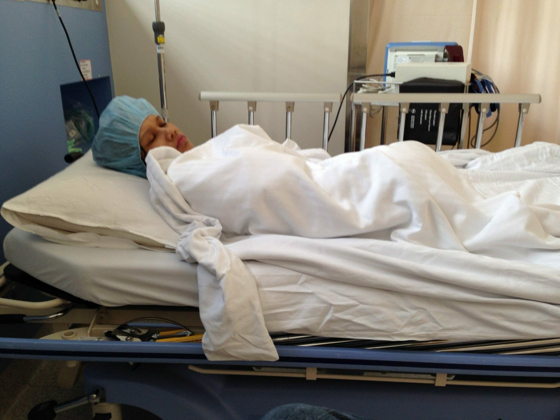 Author lying on a hospital bed wrapped in a blanket.