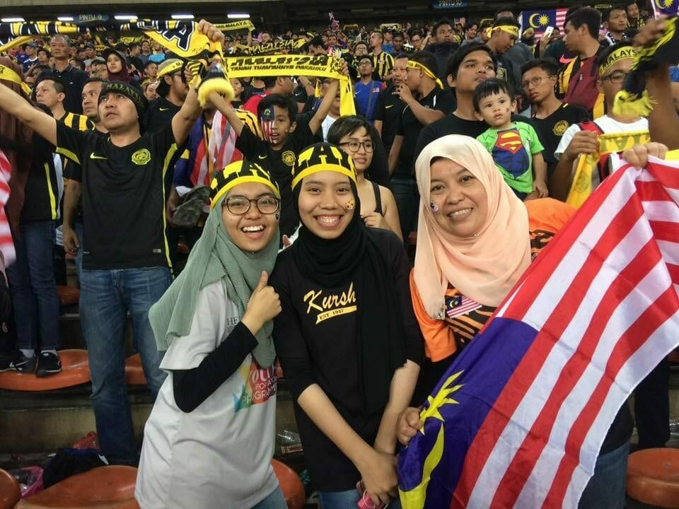 People cheering and waving the Malaysian flag during a sporting event.