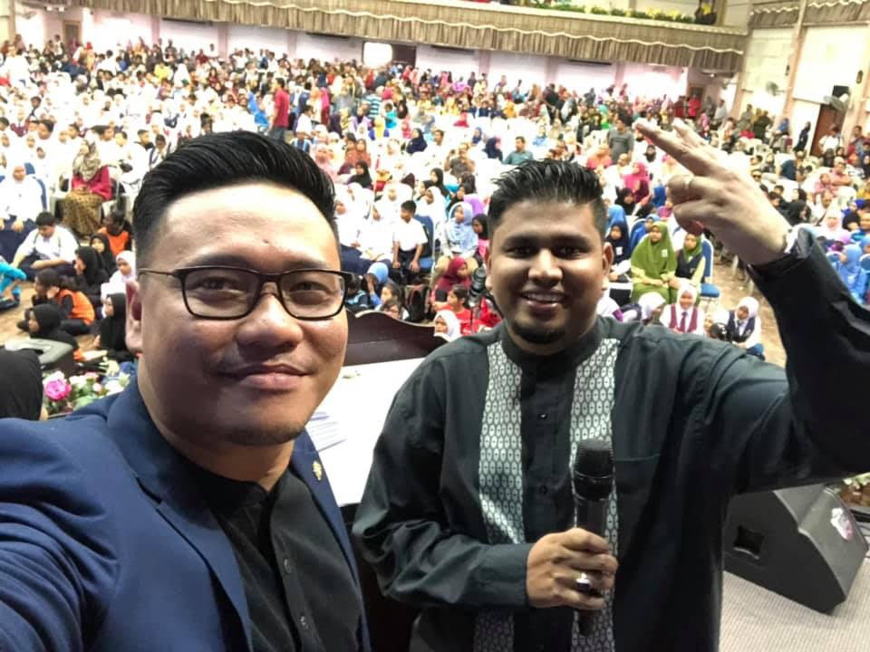 Cikgu Lan (pictured right) with his students behind him.