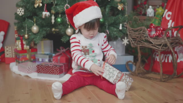 hand hold shoot toddler baby girl open gift box in front of Christmas tree