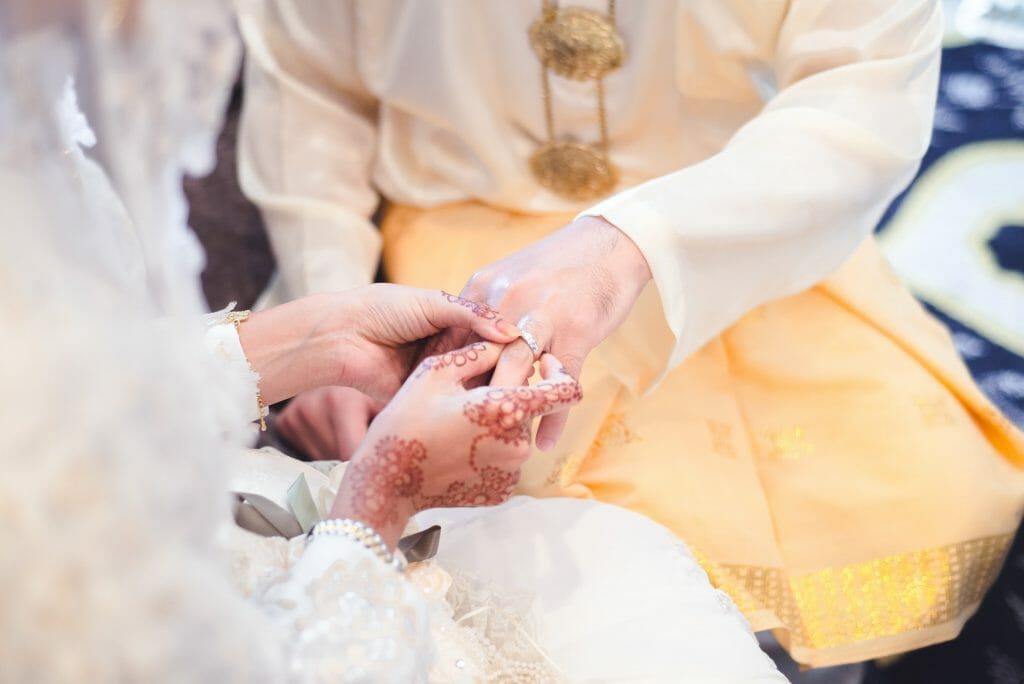 Couple getting married putting a ring on each other's fingers