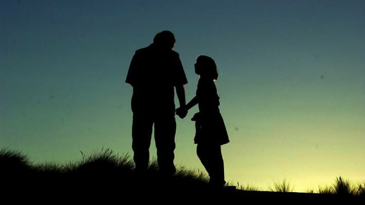 Daughter pleading with her father while taking his hand silhouette against a sunset