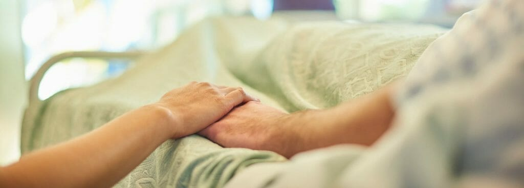 Hospital bedside holding a patient's hand to give support