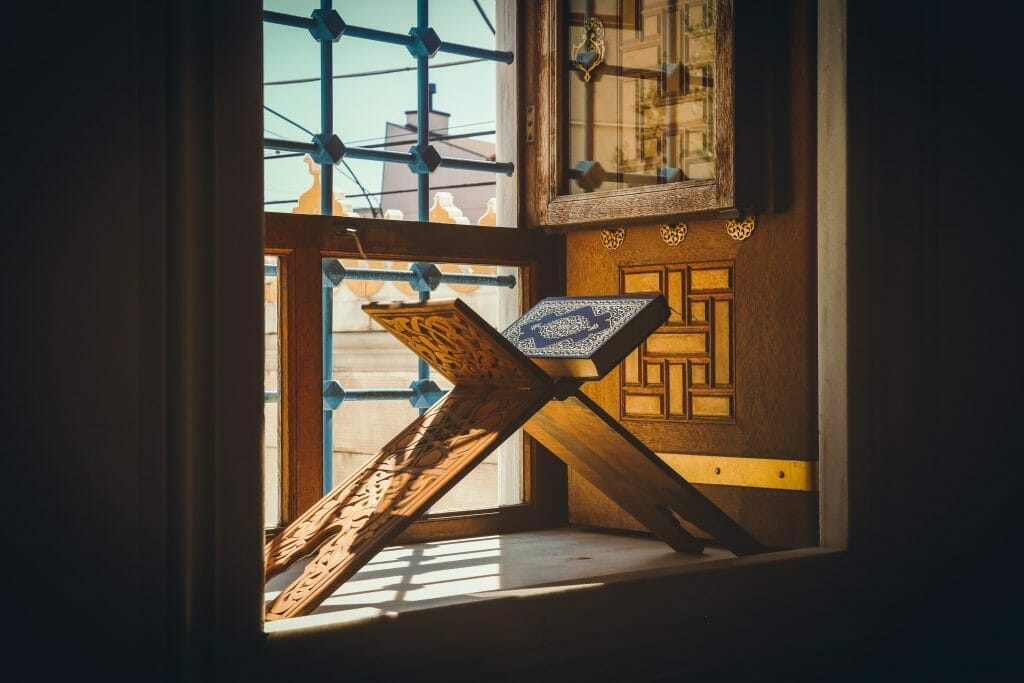 Quran laid on a podium by the window while afternoon sunlight shines in