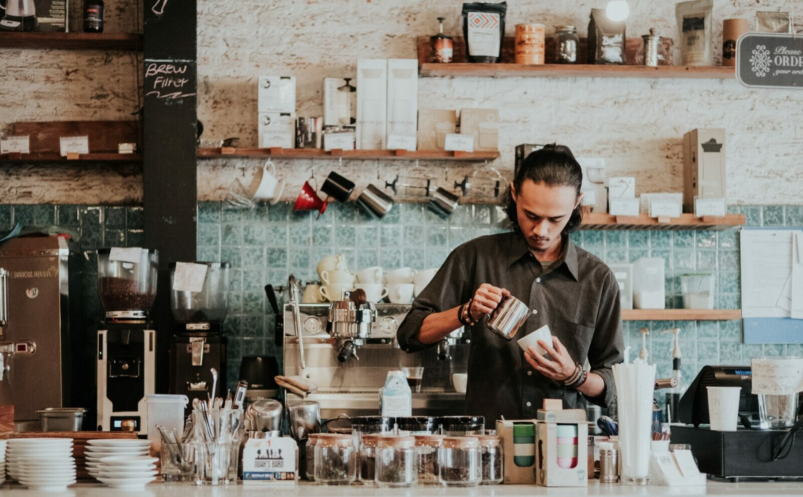 A local man pouring coffee as a barista