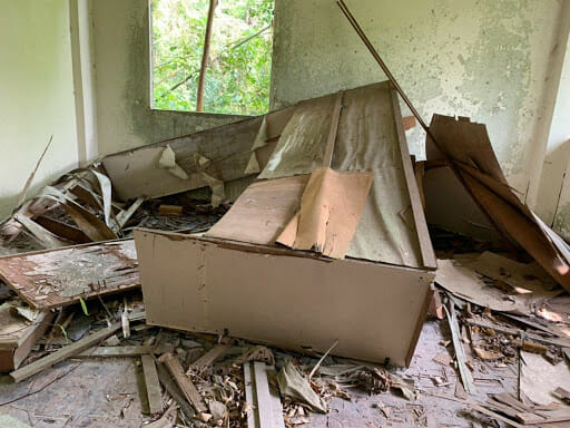 Fallen cupboards and broken woodwork in various degrees of dilapidation.