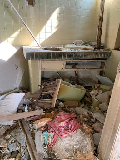 The looters would remove the toilet seats and wall portions to uncover and strip away the metals, and then dump the leftover broken ceramics and bricks in the kitchen.