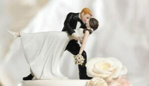 A married couple kissing on top of a wedding cake