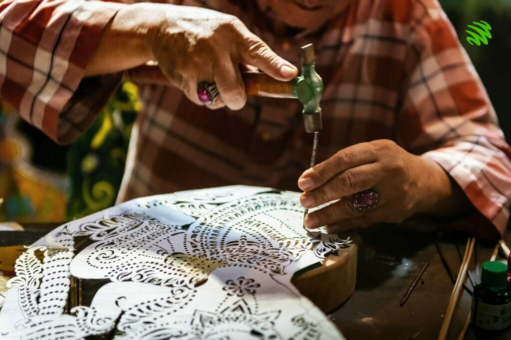 A practitioner of Wayang Kulit working on an intricate design of his puppet