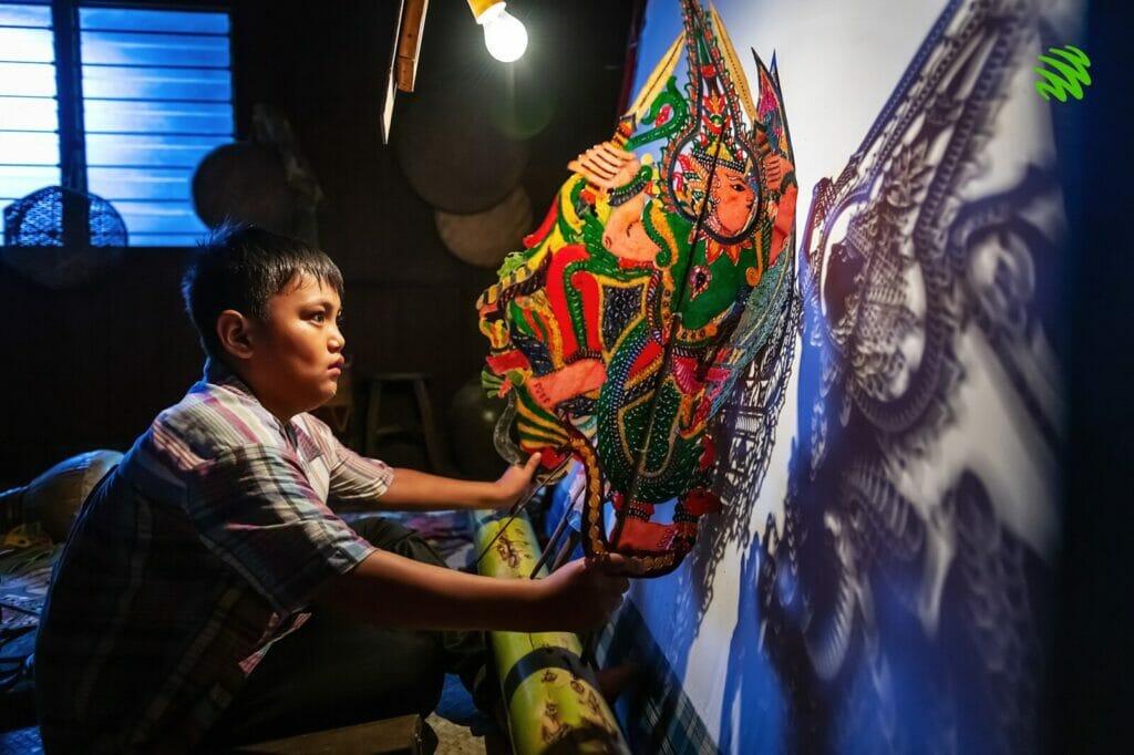 A young boy Adam Eyo plays with wayang kulit of his grandfather, Pak Cu.