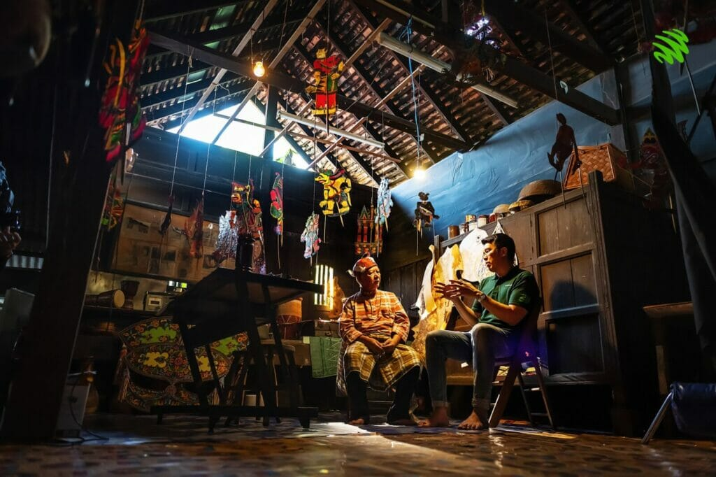 A practitioner of Wayang Kulit sits down in his house talking to an interviewer.