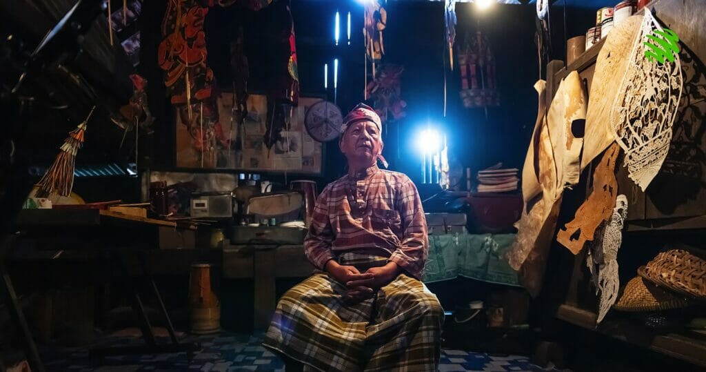 A practitioner of Wayang Kulit sits down in his house surrounded by his craft.