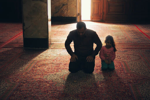 Muslim father and daughter praying.