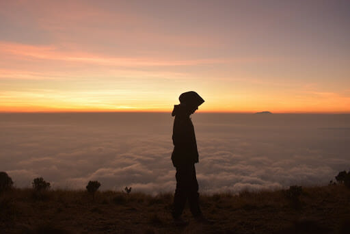 Muslim girl above the clouds silhouetted against the sunrise at dawn.
