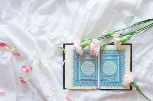Islam Quran open on a white bed, with flowers laid on top.