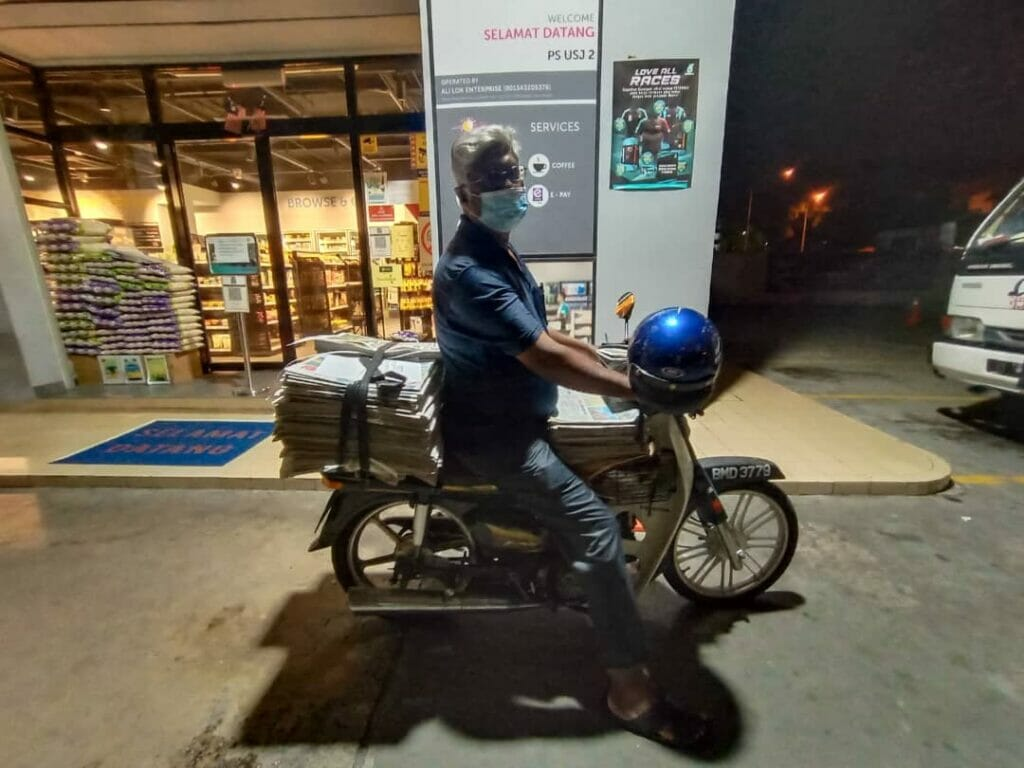Mr. Shaik Nainar, sitting astride his motorcycle with his newspaper delivery stack at 6am in the morning, outside a petrol station in USJ 2, Subang Jaya.